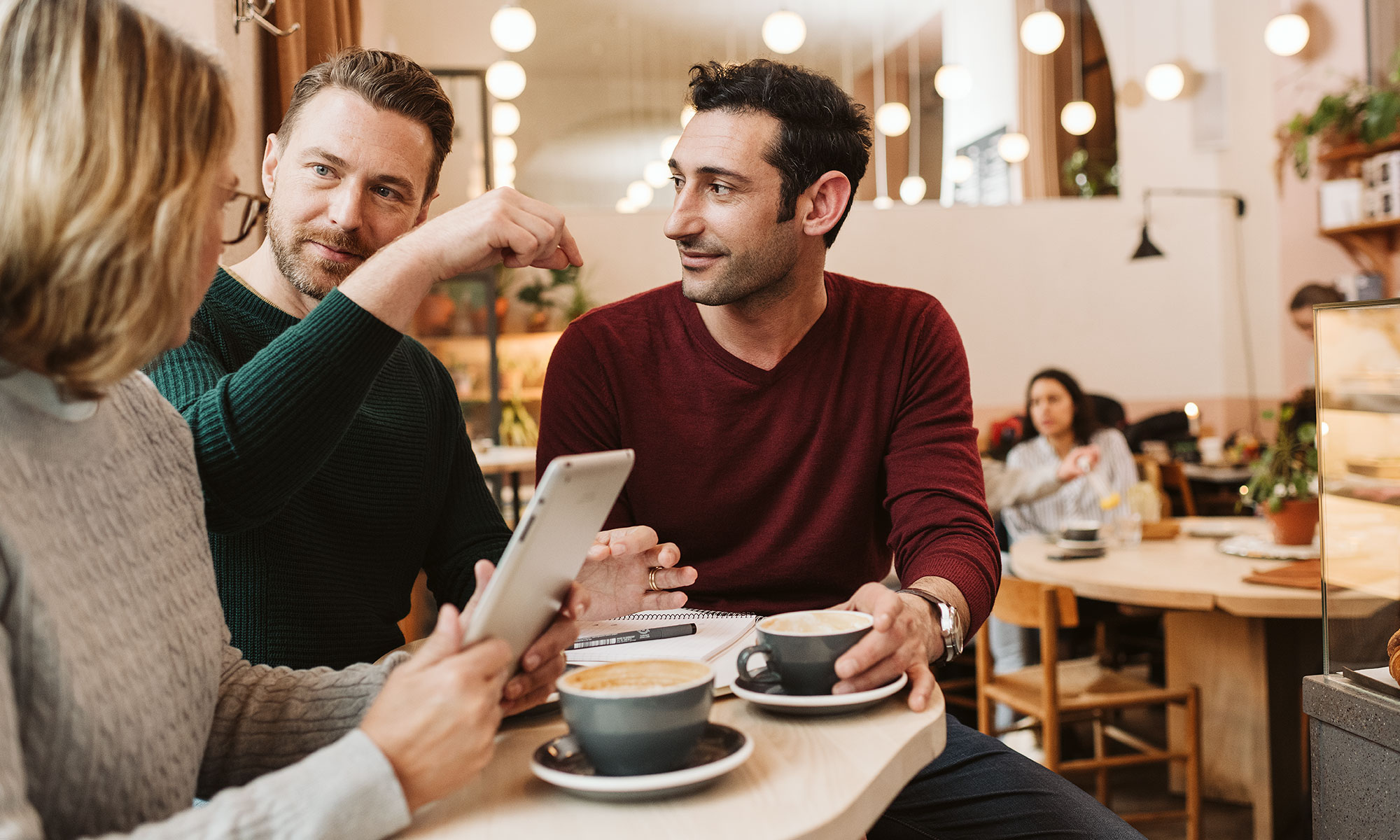 Three persons in a discussion at a café.